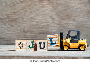 Toy forklift hold block l to complete word 9 jul on wood background (Concept for calendar date in month July)