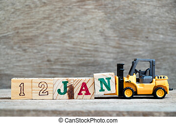 Toy forklift hold block N to complete word 12jan on wood background (Concept for calendar date in 12 month January)