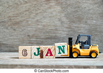 Toy forklift hold block N to complete word 6jan on wood background (Concept for calendar date in 6 month January)