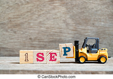 Toy forklift hold block P to complete word 1 sep on wood background (Concept for calendar date in month September)