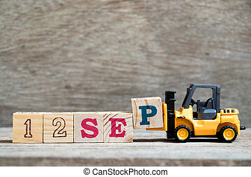 Toy forklift hold block P to complete word 12 sep on wood background (Concept for calendar date in month September)