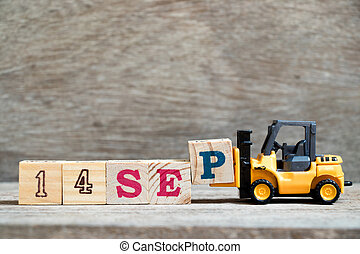 Toy forklift hold block P to complete word 14 sep on wood background (Concept for calendar date in month September)