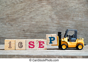 Toy forklift hold block P to complete word 16 sep on wood background (Concept for calendar date in month September)