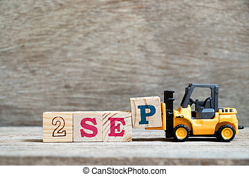 Toy forklift hold block P to complete word 2 sep on wood background (Concept for calendar date in month September)