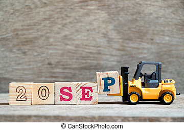 Toy forklift hold block P to complete word 20 sep on wood background (Concept for calendar date in month September)
