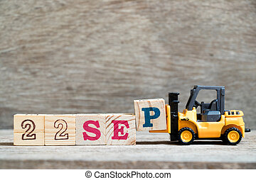 Toy forklift hold block P to complete word 22 sep on wood background (Concept for calendar date in month September)