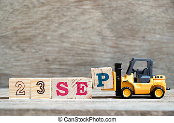 Toy forklift hold block P to complete word 23 sep on wood background (Concept for calendar date in month September)