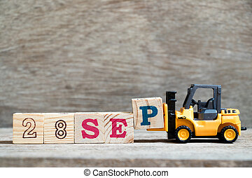 Toy forklift hold block P to complete word 28 sep on wood background (Concept for calendar date in month September)