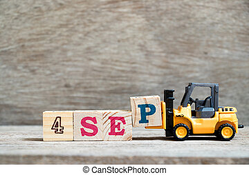 Toy forklift hold block P to complete word 4 sep on wood background (Concept for calendar date in month September)