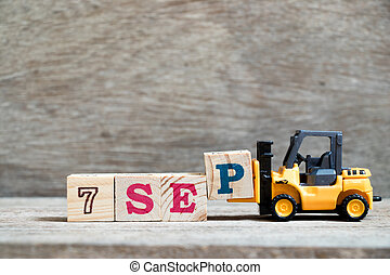 Toy forklift hold block P to complete word 7 sep on wood background (Concept for calendar date in month September)