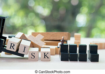 Toy forklift hold block to complete word RISK set to miniature businessman