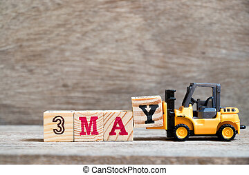 Toy forklift hold block Y to complete word 3 may on wood background (Concept for calendar date for month May)