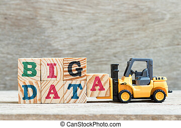 Toy forklift hold lette block a to complete word big data on wood background