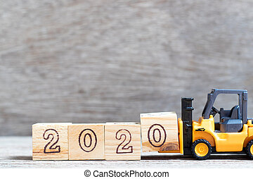 Toy forklift hold letter block 0 in word 2020 on wood background
