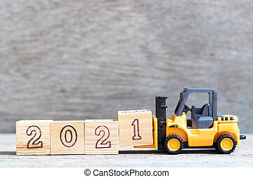 Toy forklift hold letter block 1 in word 2021 on wood background
