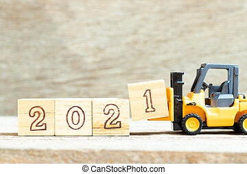 Toy forklift hold letter block 1 to complete word 2021 on wood background