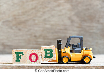 Toy forklift hold letter block B in word FOB (abbreviation of Free On Board) on wood background