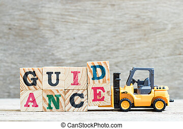 Toy forklift hold letter block d, e to complete word guidance on wood background