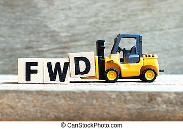 Toy forklift hold letter block D to complete word FWD (Abbreviation of forward) on wood background