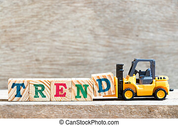 Toy forklift hold letter block d to complete word trend on wood background