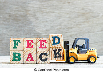 Toy forklift hold letter block d,k to complete word feedback on wood background
