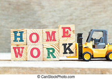 Toy forklift hold letter block e and k to complete word homework on wood background