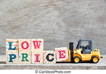 Toy forklift hold letter block E to complete word low price on wood background