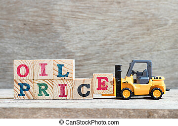 Toy forklift hold letter block e to complete word oil price on wood background
