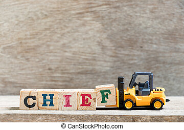 Toy forklift hold letter block f in word chief on wood background