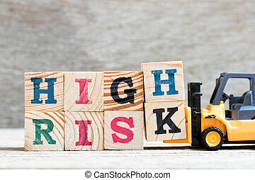 Toy forklift hold letter block H,K to complete word high risk on wood background