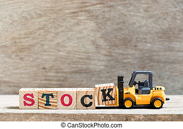 Toy forklift hold letter block k in word stock on wood background