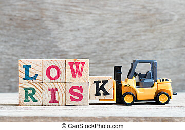 Toy forklift hold letter block K to complete word low risk on wood background