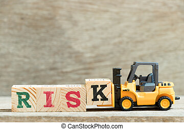 Toy forklift hold letter block k to complete word risk on wood background