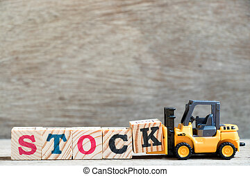 Toy forklift hold letter block K to complete word stock on wood background
