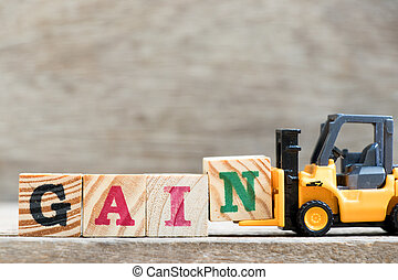 Toy forklift hold letter block N in word gain on wood background