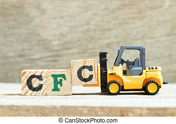 Toy forklift hold letter block to complete word Alphabet letter in word CFC (abbreviation of Chlorofluorocarbon) on wood backgroundon wood background