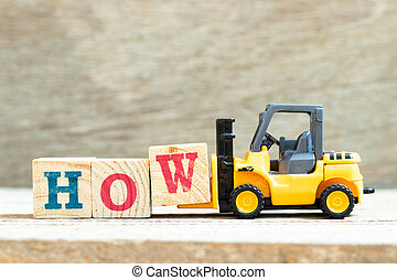 Toy forklift hold letter block w to complete word how on wood background