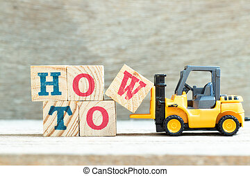 Toy forklift hold letter block w to complete word how to on wood background