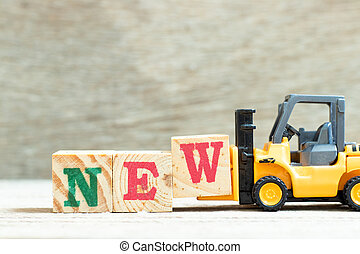 Toy forklift hold letter block w to complete word new on wood background