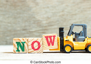 Toy forklift hold letter block w to complete word now on wood background