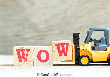 Toy forklift hold letter block w to complete word wow on wood background