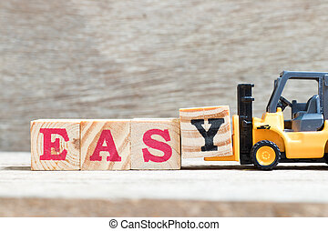 Toy forklift hold letter block y in word easy on wood background