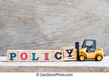 Toy forklift hold letter block y to complete word policy on wood background