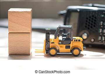Toy forklift truck and wooden block with radio communication background. Concept of international freight transport