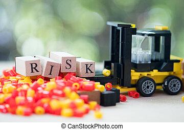 Toy forklift with letter block RISK. Concept of risk assessment