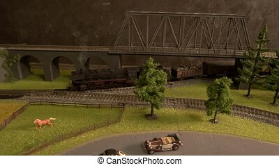 Toy freight train moving on railroad under the bridge.