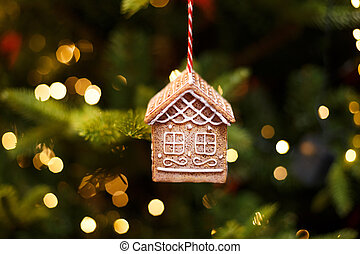 Toy gingerbread house hanging on the Christmas tree