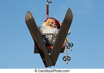 Toy gnome-skier on a background of blue sky