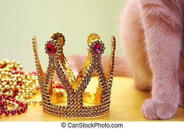 Toy Golden crown, Christmas beads pile and part of a red cat close-up. Pets and holidays.