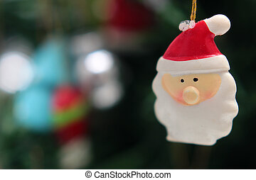 toy head Santa Claus on the Christmas tree background closeup